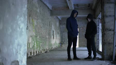банда : Boys in hoodie talking in ruined building, teenage gang, young criminals