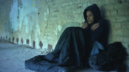 runaway : Upset homeless teenager wearing hoodie, people passing by indifferently, poverty Stock Footage