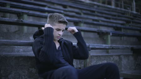 хулиган : Upset boy sitting on stadium tribune, feels depression, loneliness and sorrow