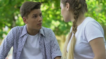resentment : Teenage couple in love quarreling outdoors, jealousy in relationship.