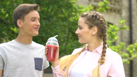 камедь : Happy teenage couple having fun together, chewing gum, drinking soda. Стоковые видеозаписи