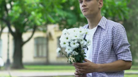 impatience : Boy holding flowers, waiting for girlfriend on date, nervous, insecure teenager