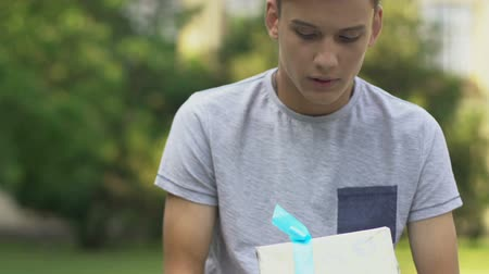 wrapped up : Teenage boy holding present, waiting for girlfriend, nervous about first date
