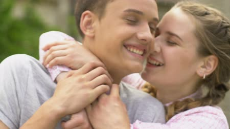 prospect : Girl running up and hugging guy, couple looking at camera. Stock Footage