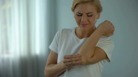 肘 : Blond woman suffering from elbow pain, holding her aching arm, injury and cramp 動画素材