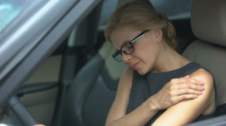the inflammation : Lady suffering from shoulder pain while sitting in car, joint inflammation