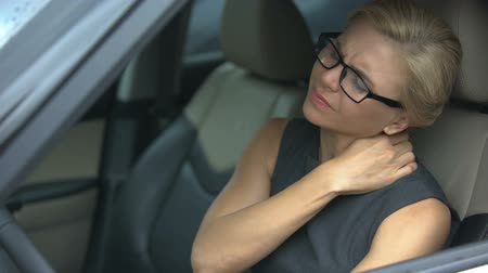 ból pleców : Stressed businesswoman suffering neck discomfort, sitting in car, sedentary life