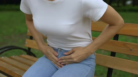 menstruáció : Female walking in park and feeling abdomen pain sitting down on bench, cystitis. Stock mozgókép