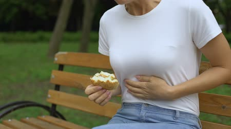 torzó : Woman eating burger in park, feeling nausea, food poisoning symptom, gastritis Stock mozgókép