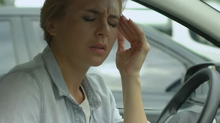 dor de cabeça : Woman in car worrying about personal problems, divorce, stressful job.