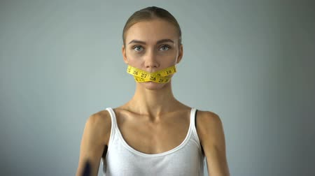 restraint : Woman crossing fork and knife, mouth closed with tape, self-restriction in food Stock Footage