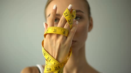 restraint : Anorexic model holding measuring tape, concept of harsh self-restriction in food