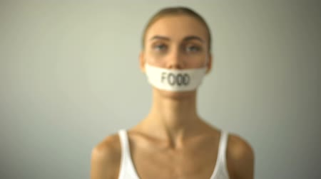 restraint : Thin model with taped mouth, concept of food restriction and anorexia. Stock Footage