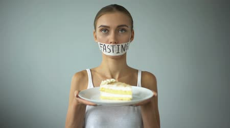 restraint : Anorexic girl holding pie, fasting word written on taped mouth, ban on sweets. Stock Footage