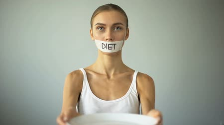 restraint : Slim girl with taped mouth showing empty plate, severe diet and self-destruction Stock Footage