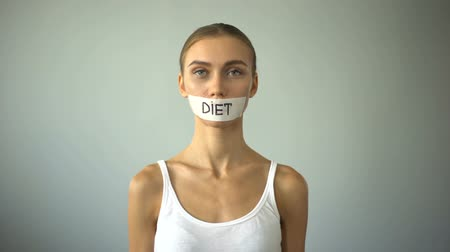 restraint : Diet word written on taped mouth of anorexic model, severe diet, health problems Stock Footage