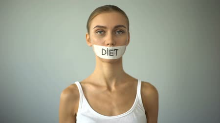 restraint : Thin girl with taped mouth holding plate with tomato, exhausting diet, anorexia. Stock Footage