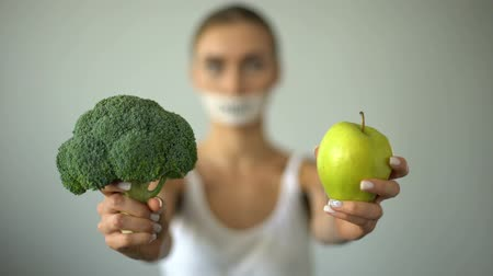 rekomendacja : Vegan with taped mouth holds vegetables, concept of severe diet, harm to health Wideo