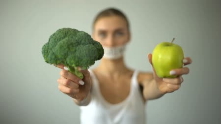 restraint : Anorexic model with taped mouth holding vegetables, concept of excessive fasting Stock Footage