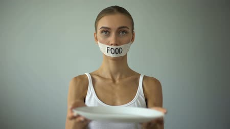 restraint : Skinny girl with taped mouth showing empty plate, concept of hunger and anorexia