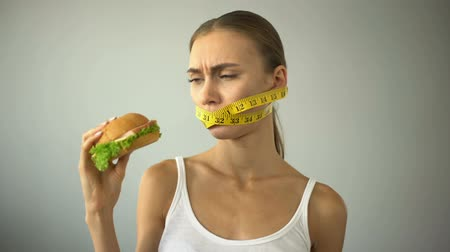 restraint : Anorexic girl ties mouth with tape-line, fights with temptation to eat burger
