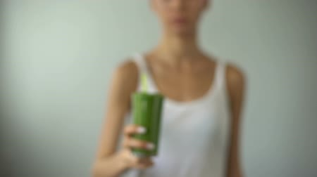 diety : Girl holding green smoothie for weight loss, vegetable juice, healthy diet