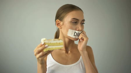 korlátozás : Lean girl fights temptation to eat pie, bites piece, sugar cravings, calories Stock mozgókép