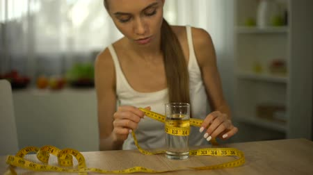 obsession : Anorexic girl measuring glass of water with tape, exhausted body, obsession