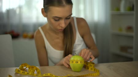 restraint : Anorexic girl measuring apple with tape, counting calories and body mass index