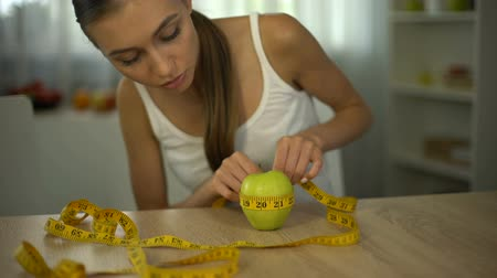 restraint : Girl measuring apple with tape line, counting calories, organic food and diet Stock Footage