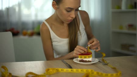 restraint : Girl measuring piece of cake with tape, fear of gaining weight, food restriction Stock Footage