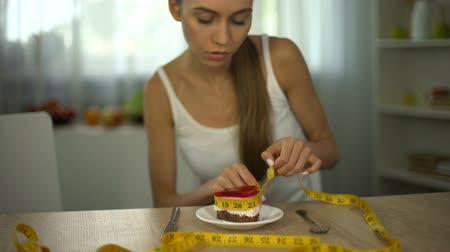 restraint : Underweight girl measuring piece of cake with tape, fear of gaining weight
