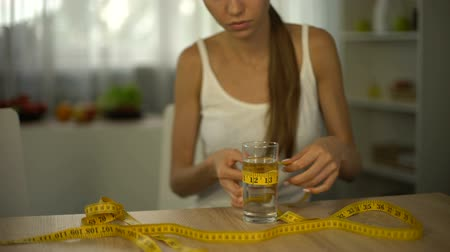 restraint : Girl measuring glass of water with tape, starving body, exhaustion, anorexia Stock Footage