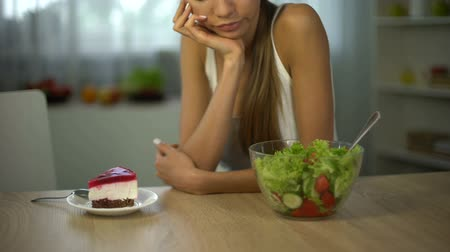 углеводы : Girl chooses cake instead of salad, quits exhausting diet, sugar for body energy Стоковые видеозаписи