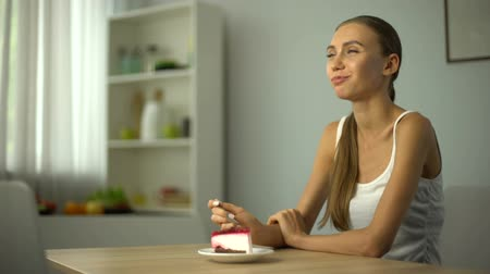 decidir : Lean girl eating cake, hand holds out tape, conscience resembles about calories Stock Footage