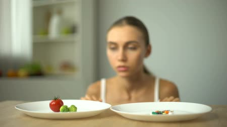 bulimia : Girl choosing between vegetables and pills, healthy diet vs weight loss drugs