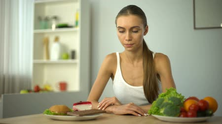 решить : Slim girl choosing between junk food and healthy vegetables, hesitation.