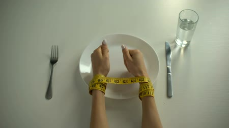 restraint : Hands tied with tapeline on empty plate, girl obsessed with counting calories Stock Footage