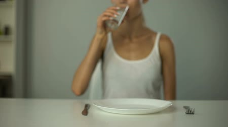 self harm : Anorexic girl sitting in front of empty plate, drinking water, severe diet