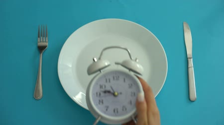 ajánlás : Alarm clock on plate, adhere to diet time, proper nutrition, discipline, closeup Stock mozgókép