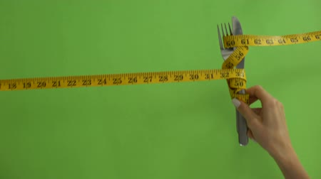 сантиметр : Knife and fork tied with measuring tape, concept of strict food restrictions Стоковые видеозаписи