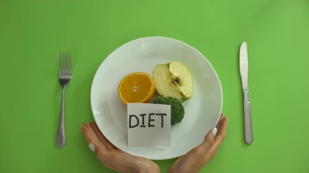 obsession : Diet note on plate with fruits and vegetables, hands tied with measuring tape