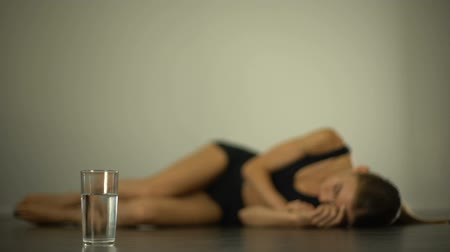 morrer : Anorexic girl lying on floor, suffering from stomach pain, nausea, bulimia