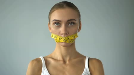 measure tape : Woman closed mouth with tape-line, crossing fork and knife, stop diet, anorexia