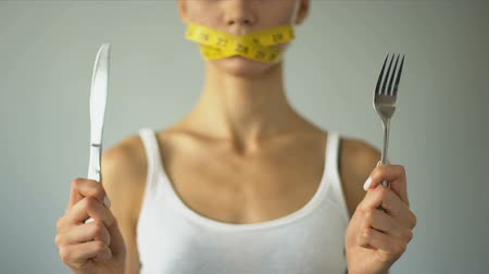 measure tape : Slim girl closed mouth with tape, holding fork and knife, excessive self-control Stock Footage