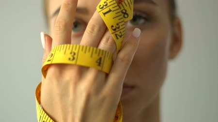 self harm : Closeup of woman closing mouth with measuring tape, bmi calculation, anorexia Stock Footage
