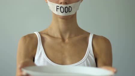 obsession : Girl with taped mouth holding empty plate, food restriction causes anorexia