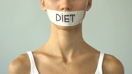 obsession : Diet written on taped mouth of slim girl, severe self-restrictions, anorexia Stock Footage
