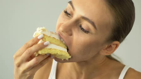 соблазнять : Girl on diet eating cake eagerly, temptation, sweets cause acne.