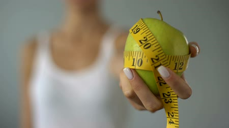 diety : Girl holding apple wrapped in measuring tape, calculation of calories, diet